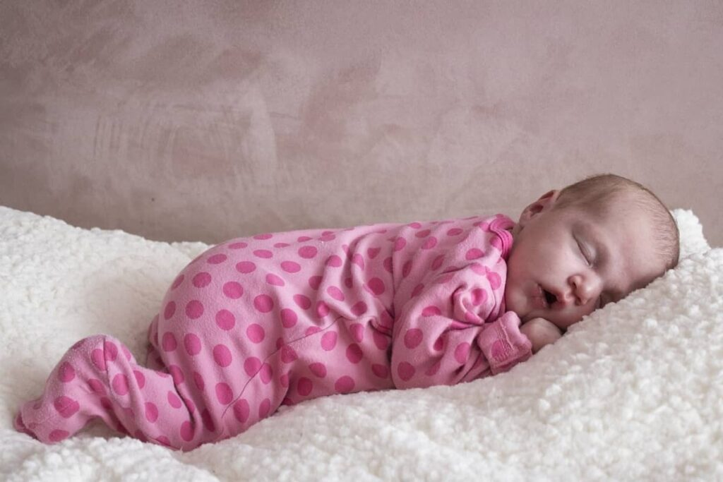 baby sleeping on soft bed
