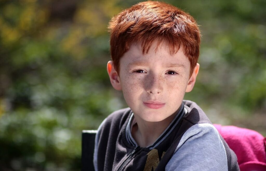 boy-red-hair-in-leafy-background
