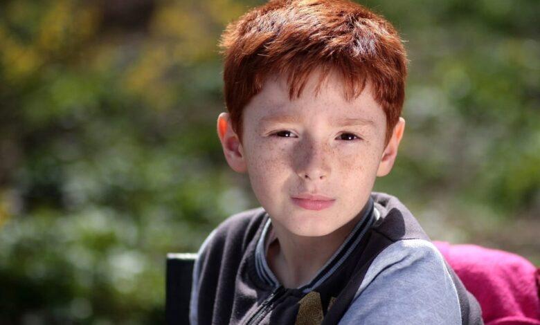 boy-red-hair-in-leafy-background